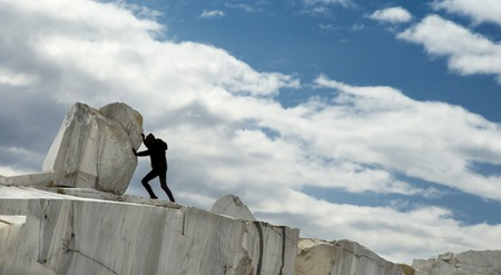 sisyphus: A small human female figure pushing a large marble stone. Sisyphus metaphor. Heavy tasks and problems concept. Stock Photo