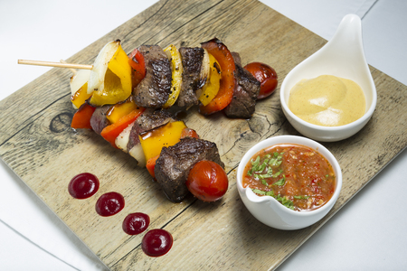 Lamb barbecue with dipping sauce on wood board