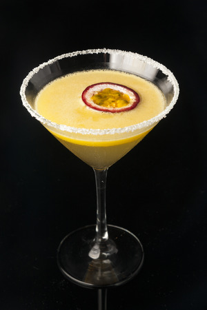 Passion fruit cocktail with black background Фото со стока
