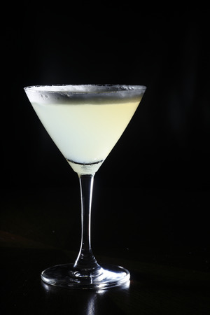 white cocktail with form on top against black background