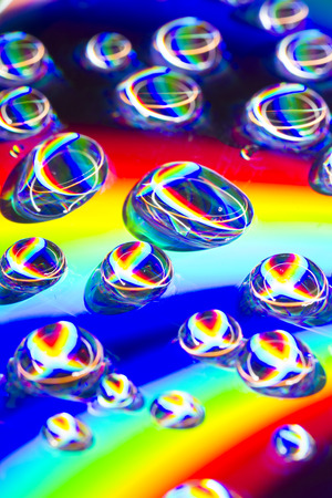 Reflect like rainbow in water drop and disk Фото со стока