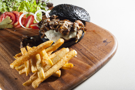 Beef charcoal burger with salad and french fried on left side of frame