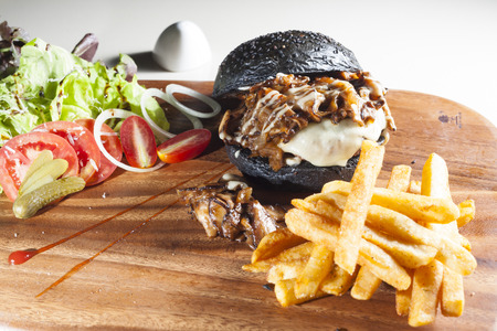 Beef charcoal burger with salad and french fried on wood board