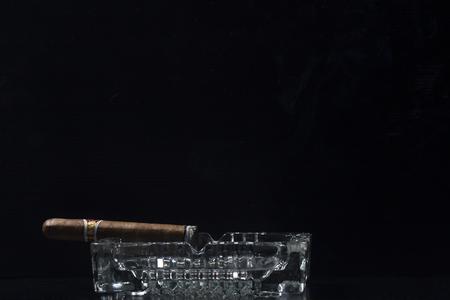 Cigar on ashtray against black background Stock fotó