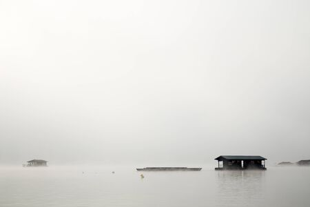 House in river cover by mist in morning