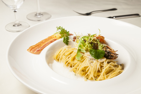 Spaghetti with tiger prawn and bacon on dining table