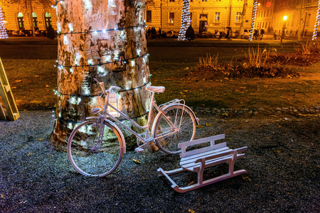 Advent in Zagreb, Christmas Market - old white bicycle, white wooden sled and tree decorated with lights in Zrinjevac park.