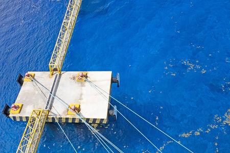 mooring bollards: Steel bridge walkway spans the sea to a harbor docking platform