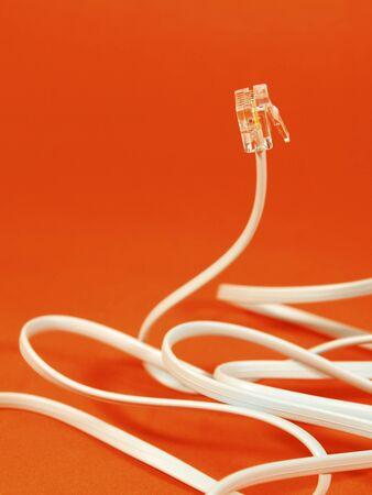 Telephone cable on orange background Stock Photo - 11792487