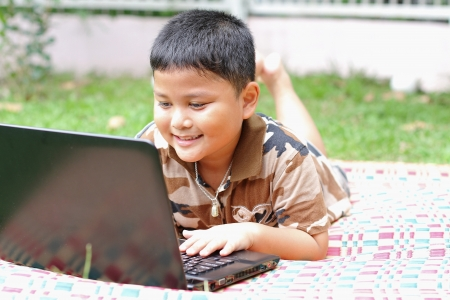 Boy playing laptop  Happily  photo