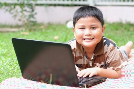 Boy playing laptop  Happily  photo