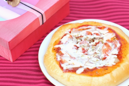 Pizza and gift boxes on red background photo