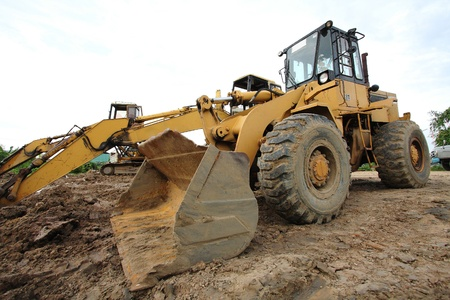 loader Excavator with backhoe unloading sand at earthmoving works in construction site