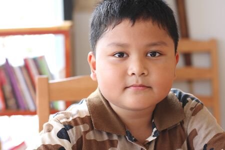 close up portrait of cute asian boy smiling photo