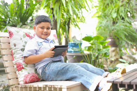 Asian boy playing tablet at the park photo