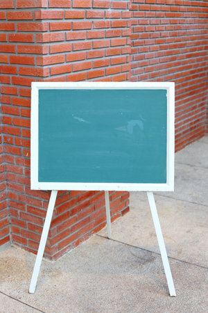 chipboard: Chalk board front red brick wall Stock Photo