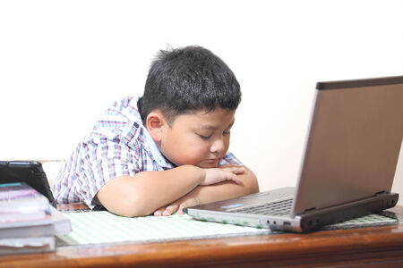 Asian boy playing computer and feel sleepy photo