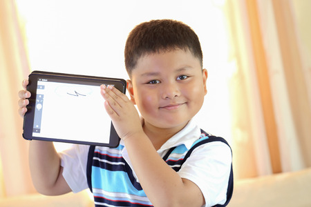 Asian boy playing Tablet fun photo