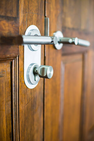 modern chrome door handle on a wooden door photo