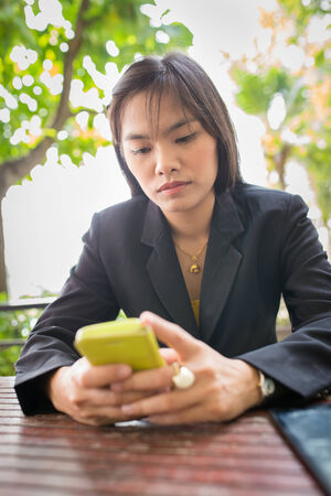 Beautiful Asian business woman using mobile for communication photo