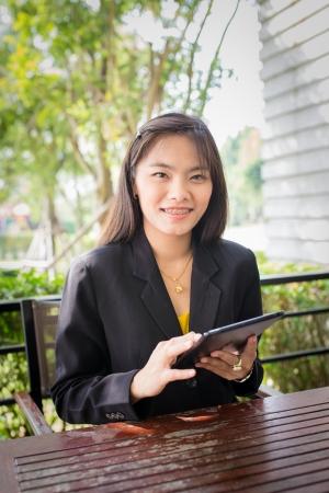 Bella donna di affari asiatica con tavoletta per la comunicazione