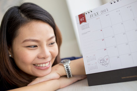 Beautiful pregnant woman looking at the calendar for the date of birth