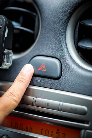 flashers: transportation and vehicle concept - man pressing red triangle car hazard warning button