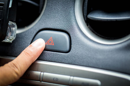 transportation and vehicle concept - man pressing red triangle car hazard warning button photo