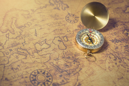antiquity: Old compass on vintage map. Stock Photo
