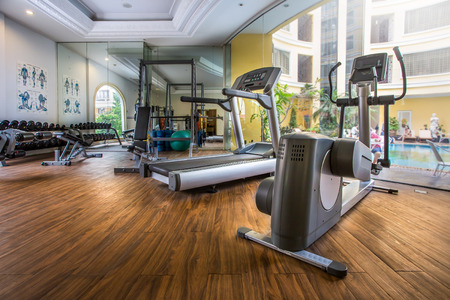 Fitness center with traineger equipments with a view to the pool Editorial