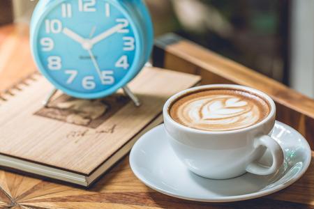 Tazza di caff� con cuore modello in un bicchiere di bianco e blu orologio sul legno Archivio Fotografico