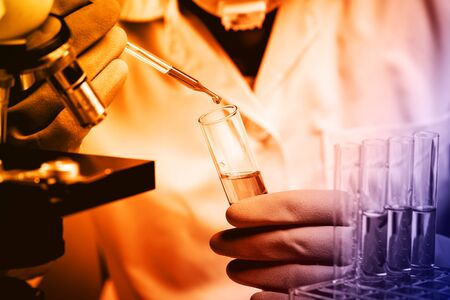 laboratory coat: Hands of clinician holding tools during scientific experiment in laboratory