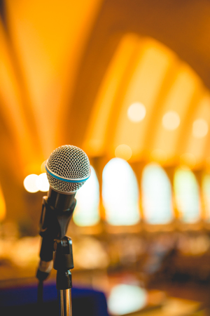 amplify: Microphone in concert hall or conference room with defocused bokeh lights in background Stock Photo