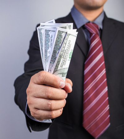 gripping: Businessman hand gripping money, US dollar (USD) bills - investment, business concepts