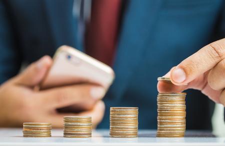 El concepto de ahorro de dinero, inversión, poniendo la mano del hombre de negocios pila de monedas de dinero creciente negocio