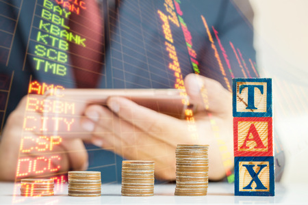 wooden block: Tax Concept with wooden block on stacked coins,Business
