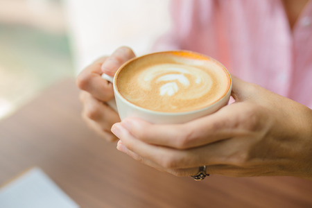 woman hands with latte on a wood table in coffee shop