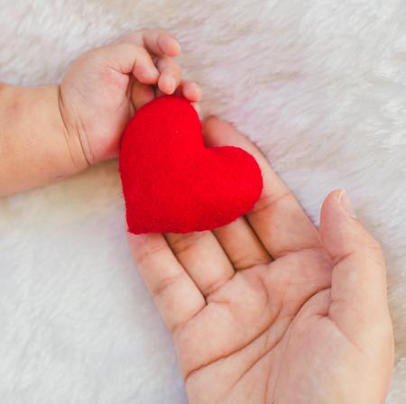 Coeur rouge en forme dans la main de maman bébé main sur blanc doux fond de couverture