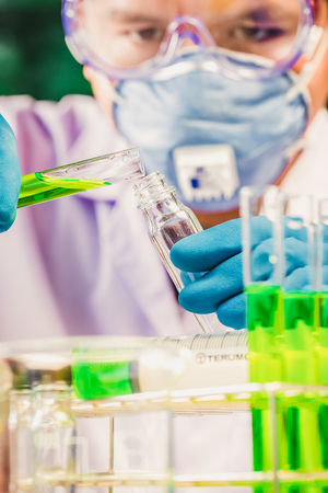 clinician: Hands of clinician holding tools during scientific experiment in laboratory,MERS Stock Photo