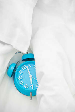 Blue alarm clock and bed