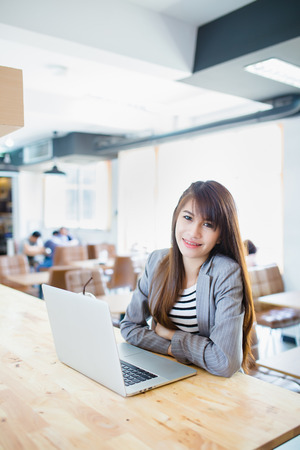 Businesswoman  using  laptop in a coffee shop,Happy
