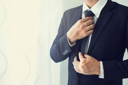 People, business,fashion and clothing concept - close up of man in shirt dressing up and adjusting tie on neck at home.