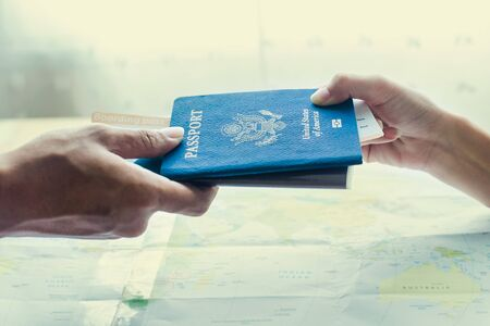 pretty travel agent giving tickets to client on map background