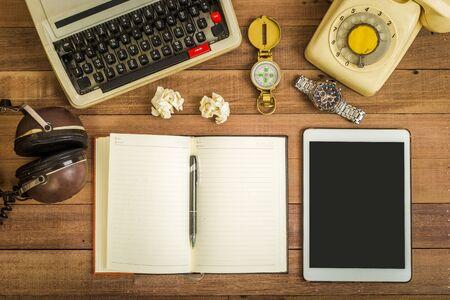 Vue de dessus du cahier sur la table en bois, machine à écrire, vieux téléphone et écouteurs