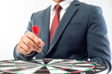 Business Man hand holding a target with darts hitting the center over white background. Concept of personal coaching success