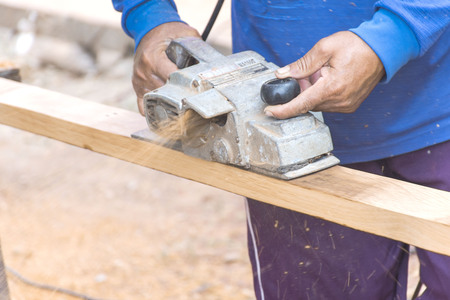 Carpenter is using electric planing machines