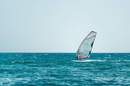 Seascape with men on surfers under sail. Windserfing