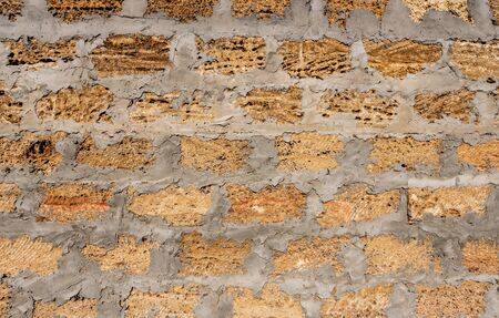 Wild stone shell rock wall texture. Uneven surface of shell rock wall. Decoration of external walls with bricks from wild stone shell rock. Stock Photo