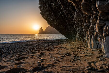 view of the sunset sea and the beach, the rock volcanic rock is lit by the warm sunset, sand and pebbles, volcanic basalt as in Iceland. Jasper beach, cape Fiolent, Crimea