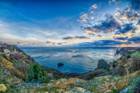 Panoramic seascape over the Jasper beach during sunset, with rocky cliff is lit by the warm sunset. Long exposure. Copy space. The concept of calmness silence and unity with nature